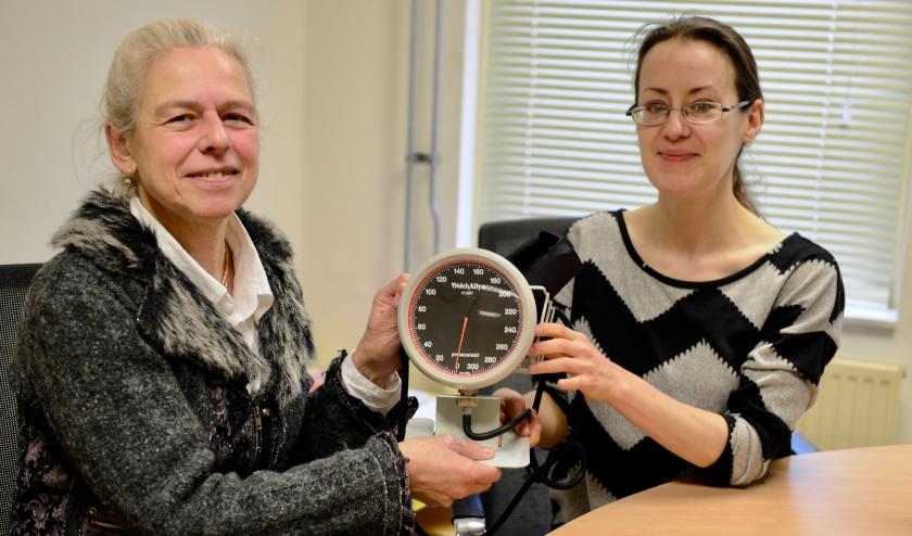 Marijke Leenhouts doet een stapje terug en draagt de verantwoording met de overhandiging van de bloeddrukmeter, over aan Vera Gondrie.