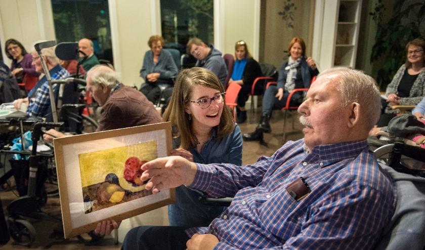 Studentdocente van OGJG geeft college kunstgeschiedenis aan ouderen.