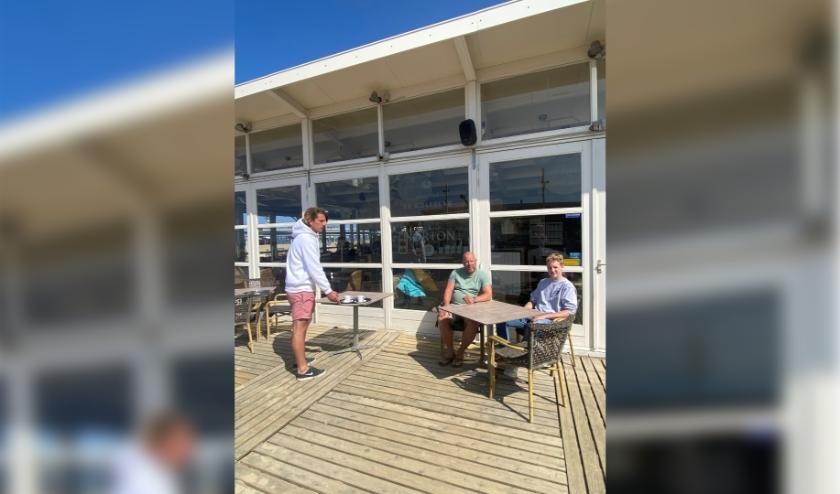 Bij strandpaviljoen De Golfslag in Scheveningen laten ze zien hoe een kopje koffie op 1,5 meter van de gasten wordt neergezet. (Foto: pr)