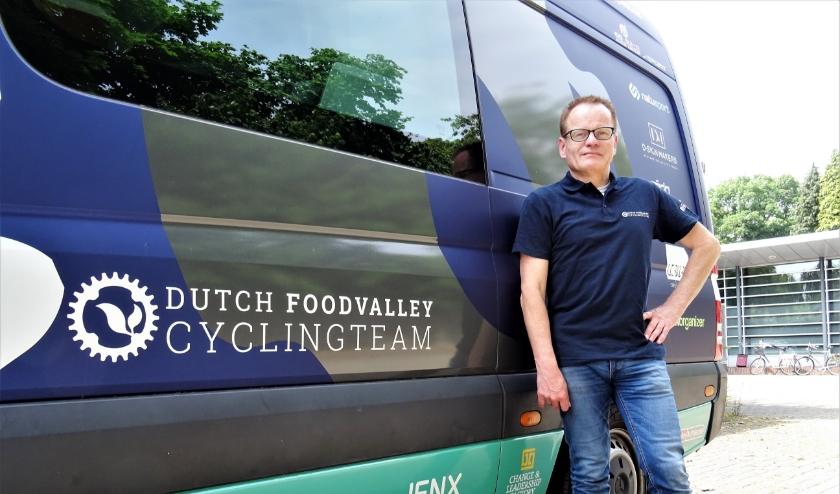 Teammager van het Dutch Food Valley Cycling Team, René Bastiaansen, poseert trots bij de nieuwe teambus.