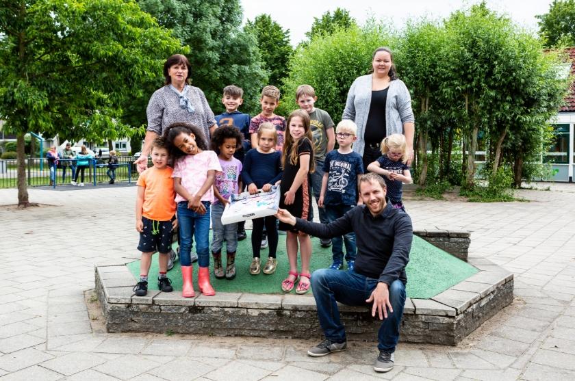 Nolda Rouwenhorst (staand links), Amanda Wissink-Klijnhout (staand rechts) en Bart Hoesté (zittend) poseren met kinderen met hun mozaïek.