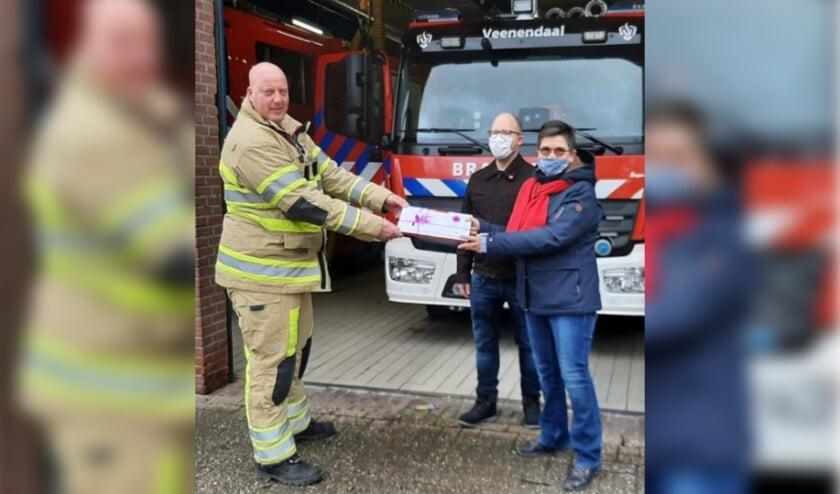 SP'ers Sietse van der Bij en Yolande de Meer overhandigen lekkers aan de brandweer.