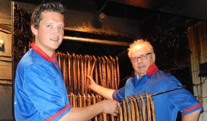 <p>Dries van den Berg (r) en zoon Peter bezig met hun geliefde ambacht: paling roken. (foto: Marco Jansen)</p>