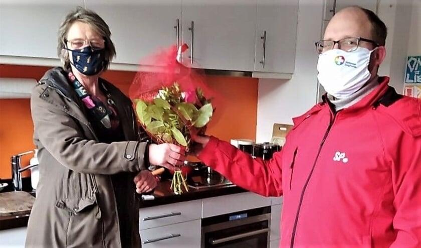 <p>Baukje Hiemstra (links) ontvangt bloemen uit handen van Sietse van der Bij.</p>
