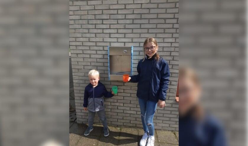 <p>Jens van de Pol en Nikki van Oeveren testen het watertappunt bij De Burcht.</p>