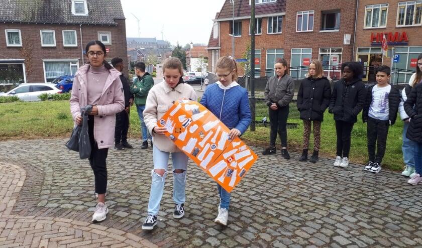 <p>Leerlingen van de Galamaschool leggen een krans en hun gedichtencollage bij het monument De Goede Herder.&nbsp;</p>