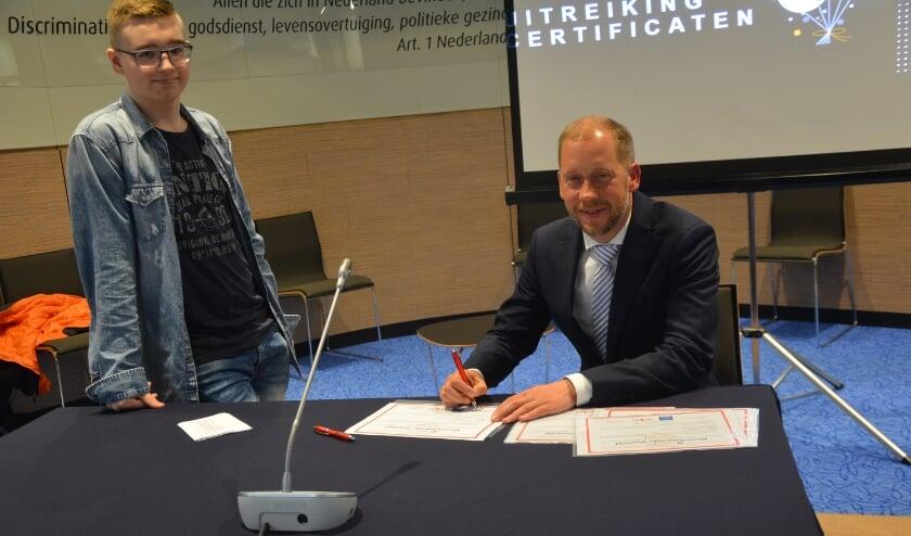 <p>Burgemeester Jan Nathan Rozendaal ondertekent het certificaat voor Nick Schenk.</p>