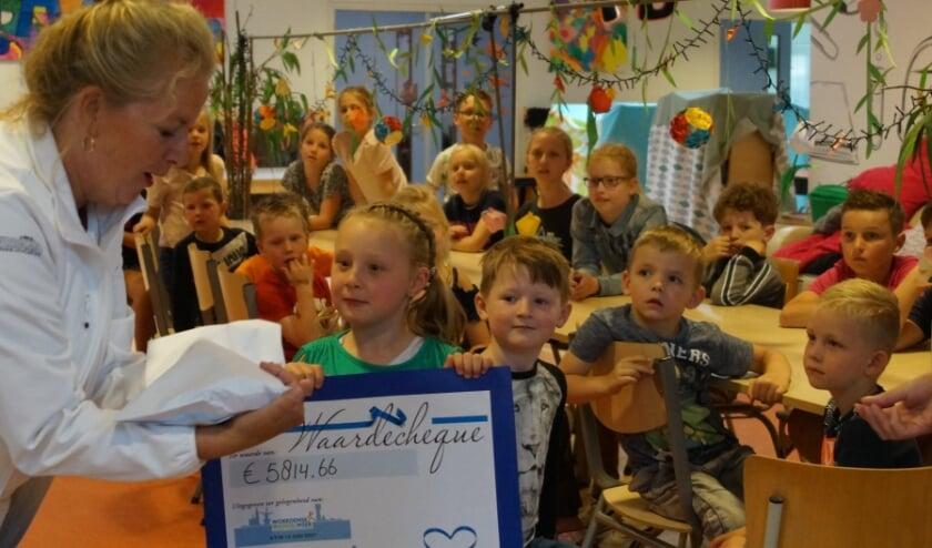 Jacqueline Engelhard van De 24 uur van Woerden laat zien hoe zwaar de enveloppen zijn met maar liefst 5.814,66 euro erin.