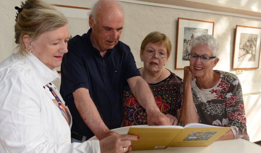 Auteur Jef de Jager laat het boek over Jan van Anrooy zien aan het bestuur van Stichting Kunst & Cultuur West Betuwe