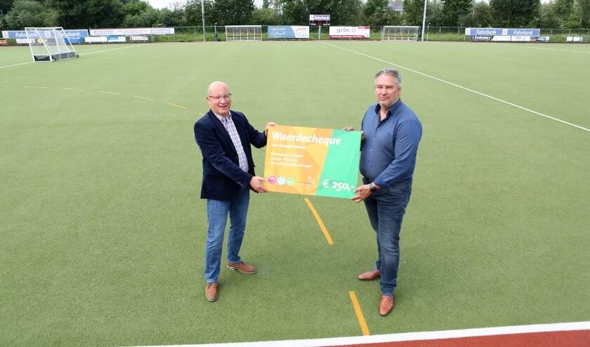 <p>Voorzitter Emiel Cellamare van De Westerduiven (links) neemt een cheque van 250 euro in ontvangst uit handen van HV Duiven-voorzitter Emiel Hartskeerl.</p>