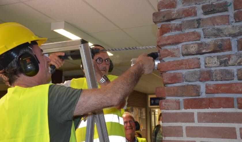 Wim Aalders en Chris Welbers ontmantelen de koker met schoolgegevens. Toon Roes kijkt toe.