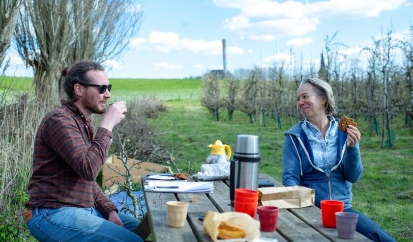 <p>Frank de Gram en Joke Feenstra picknicken in hun voedselbos De Waalgaard in Weurt. (Foto: Levien Lockefeer)</p>