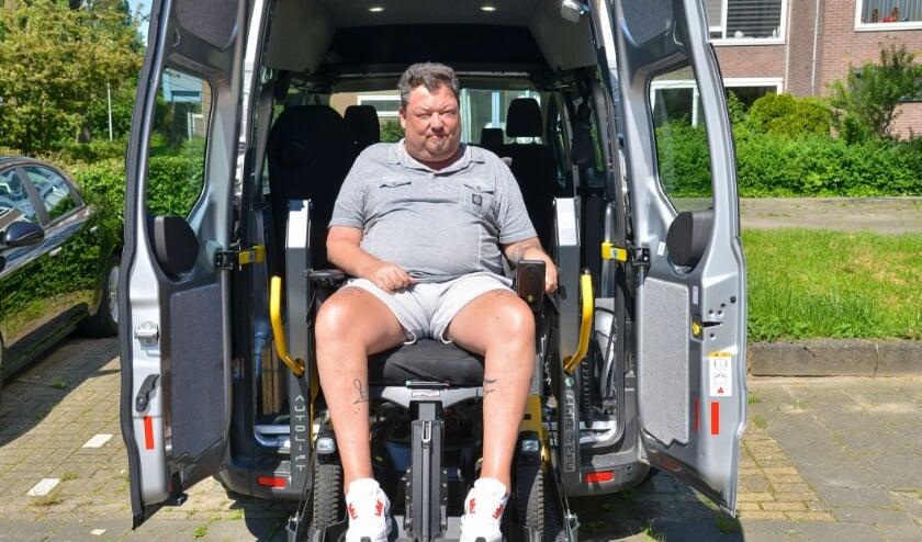 <p>Karo Murk bij de rolstoelbus van ALS Op De Weg, die hij moet inleveren omdat zijn ziekte niet progressief genoeg is. Foto: Paul van den Dungen</p>