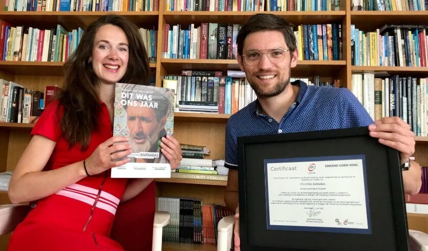 <p>Margo en Matthijs Varwijk tonen trost het nieuwe jaarmagazine en CBF-keurmerk voor hun stichting Barnabas.</p>