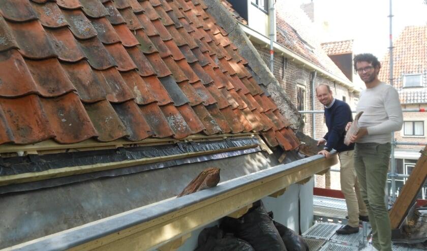 <p>Jos Snoek (links) en Ron Verduijn van Buro Stiel op een steiger aan de achterkant van hun pand, waar isolatie onder de oude dakpannen geplaatst is.&nbsp;</p>