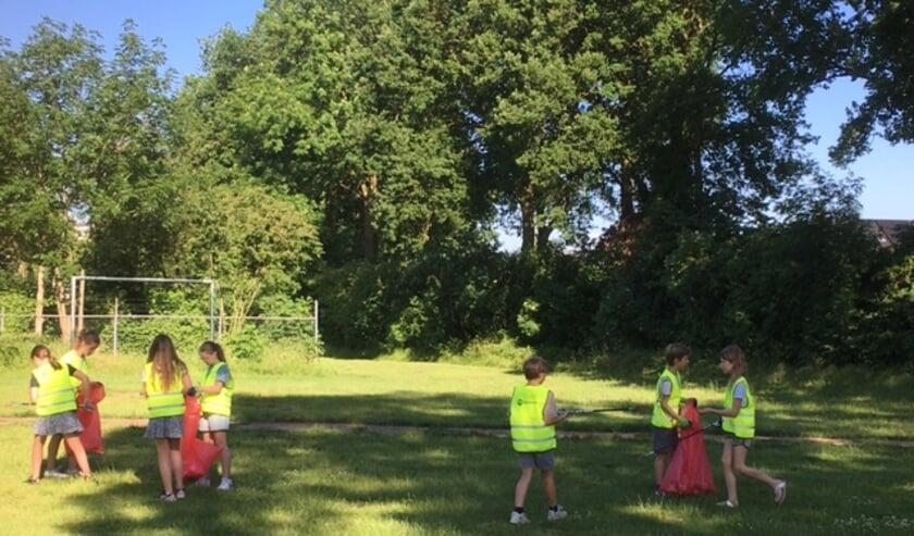 <p>Kinderen verzamelen zwerfafval.</p>