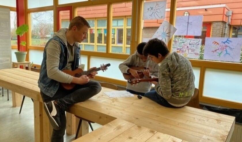 <p>Enkele kinderen van Petje Af Tiel met hun begeleider, op zondag, verdiept in een muzikale opdracht.&nbsp;</p>