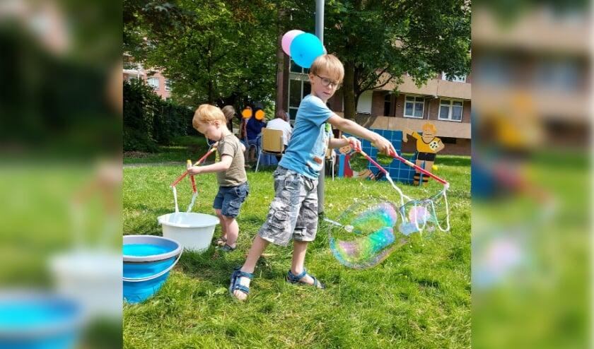 Kinderen spelen met reuzenbelleblaas op de buitenspeeldag bij De Poster