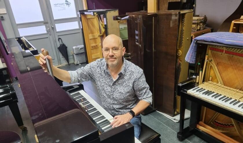 Pianotechnieker Edward Meijer in zijn werkplaats bezig de piano voor de Tilburgse stationshal te stemmen.