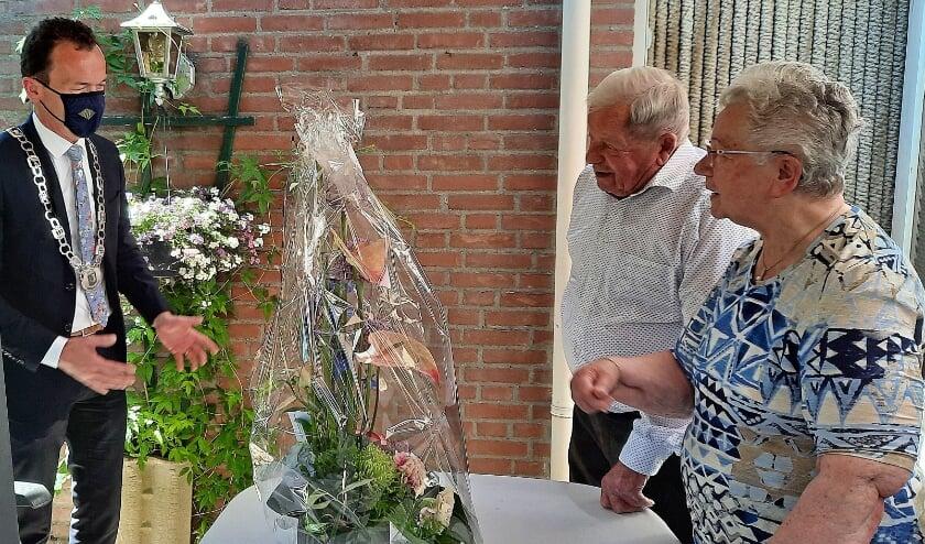 <p>Burgemeester Lucien van Rijswijk feliciteert echtpaar Reinder en Pietje de Vegt met een bloemetje voor hun 65 jarig huwelijksfeest. (foto: PR)</p>