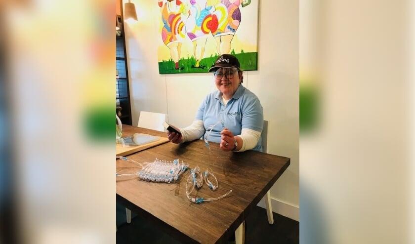 <p>&eacute;&eacute;n van de mensen met beperking, Regina van den Bos (53) . Ze is hier faceshields aan het maken. </p>