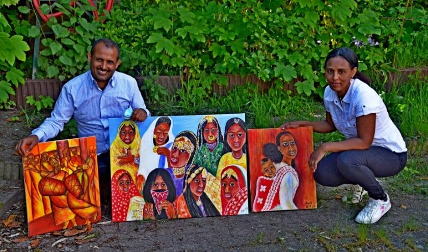 <p>Awet Afeworki en Shishay Tecle met schilderijen van Awet. Ze exposeert de hele maand juni in de bblthk (foto Jan Boer)</p>