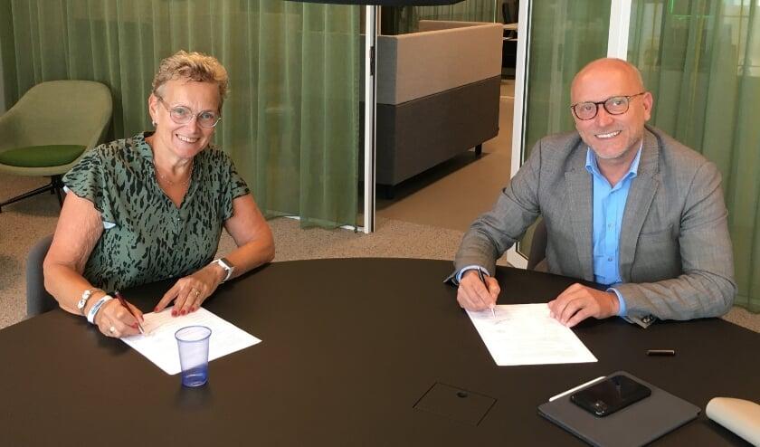 <p>Wethouder E.G. Vos – van de Weg (l.) van Oldebroek en M. Sweitser adjunct-directeur DeltaWonen ondertekenen het convenant.</p>