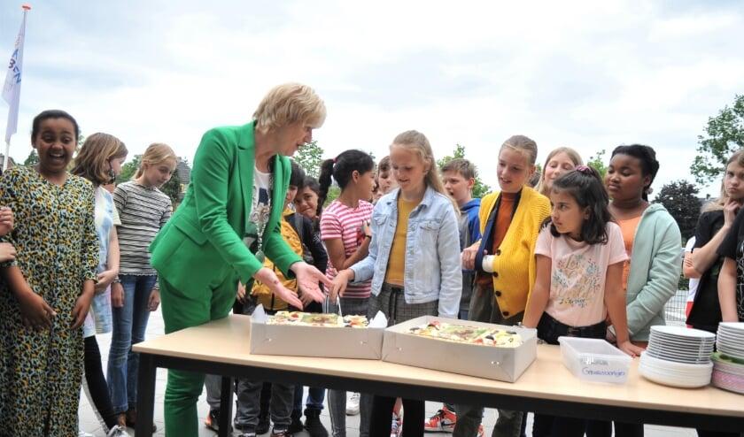 <p>De nieuwe kinderburgemeester Aline Huijgen snijdt met burgemeester Agnes Schaap een taart aan. Foto: gertbudding.nl</p>