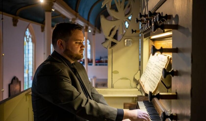 Matthijs Breukhoven aan de speeltafel van het Hess orgel in Charlois