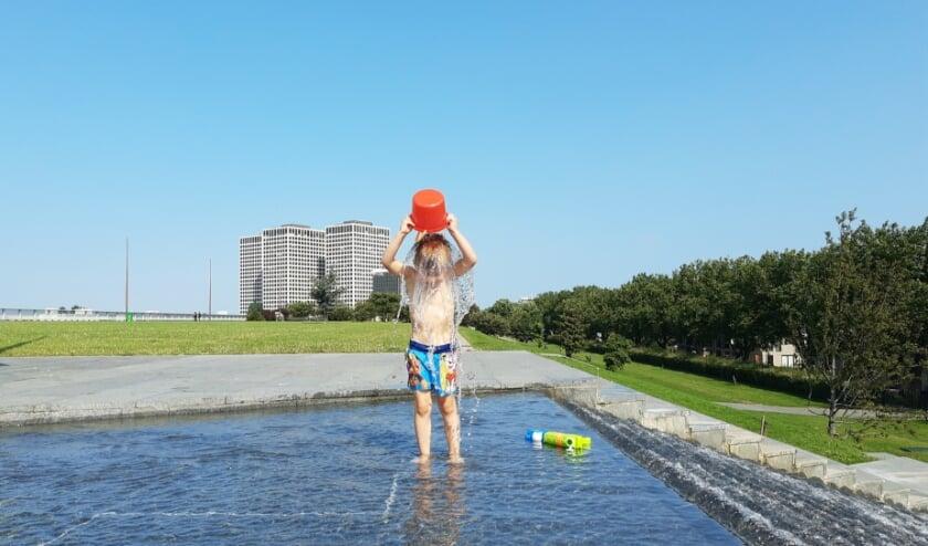 Jongetje giet emmer water over zich heen op het Dakpark