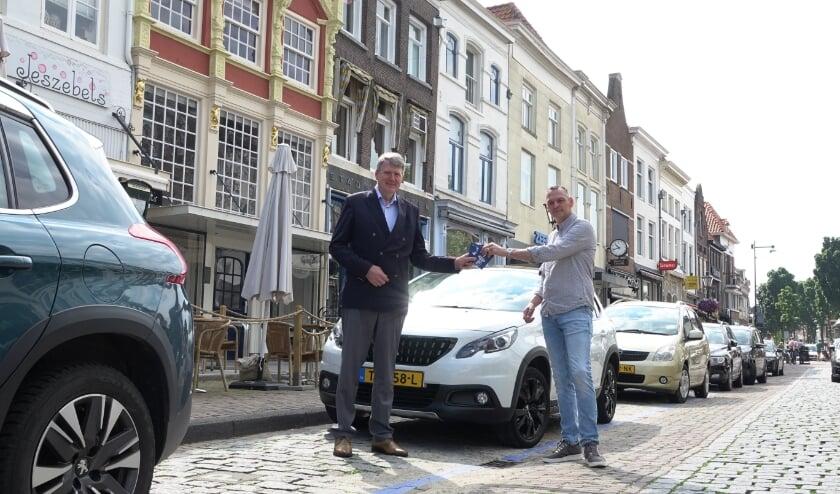 <p>Roberto Hoeppe reikt de eerste blauwe parkeerschijf uit aan wethouder Posthouwer.</p>