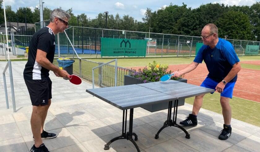 <p>Je schuift twee terrastafels tegen elkaar en je kunt tafeltennissen. Links Rob Giesen, rechts Bennie Loeters</p>