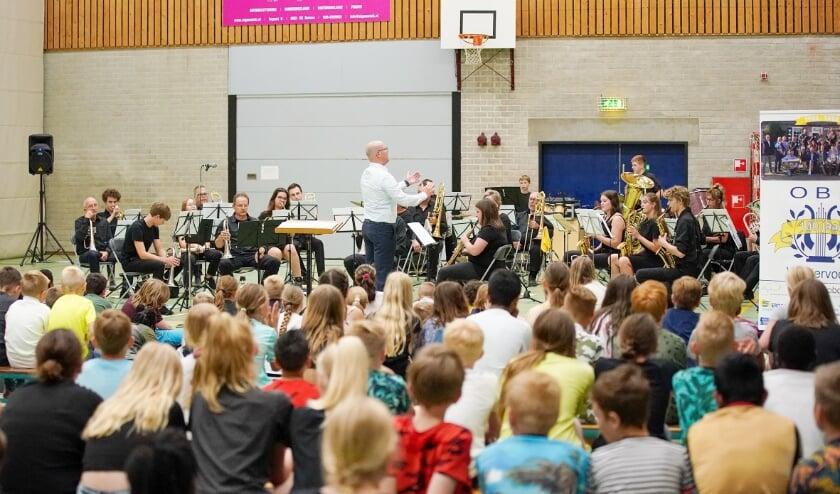 <p>Kinderen in een volle sportzaal van Sports Planet luisteren naar de klanken van fanfareorkest OBK.</p>