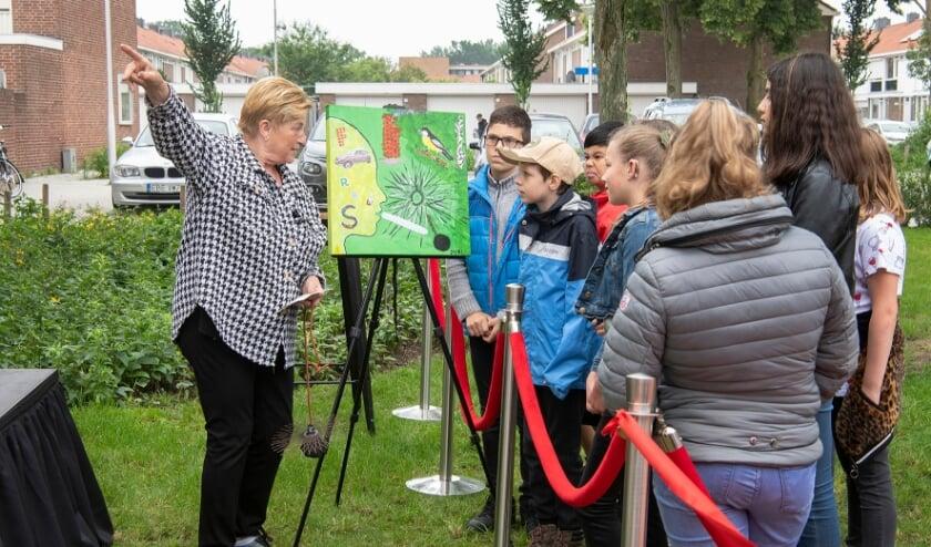 <p>Een oudere buurtbewoner vertelt aan de leerlingen over haar schilderij</p>