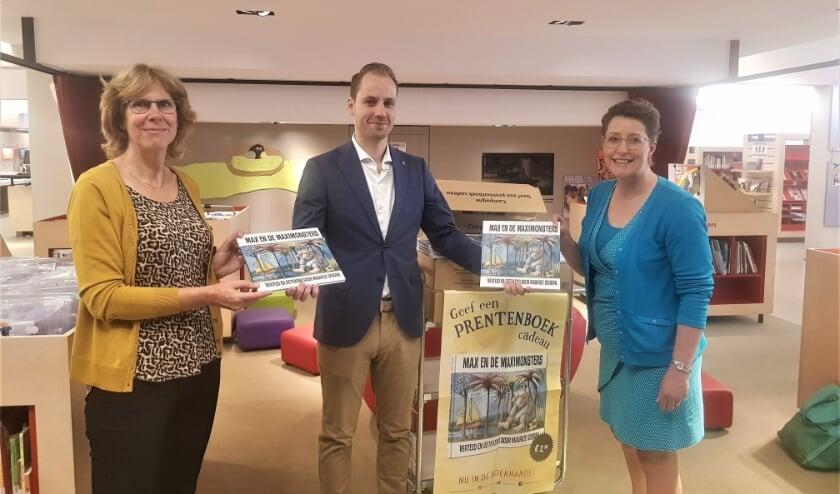 <p>Liesbeth van Brink (l) en Irini Boxma (r) nemen dankbaar de boeken in ontvangst van Juri&euml;n Koster.&nbsp;</p>