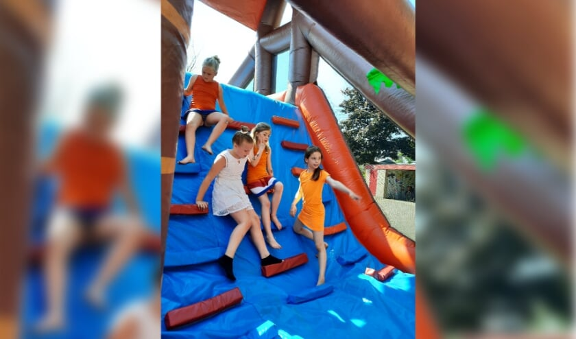 Leerlingen van de Lingelaar spelen tijdens het schoolpleinfeest op het springkussen
