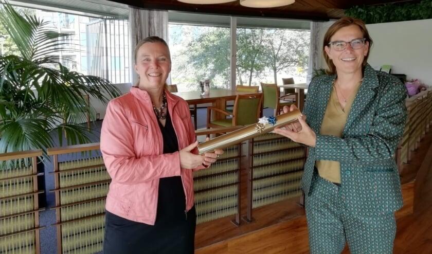 <p>Directeur-bestuurder van Woonwaarts Esther Lamers (rechts) overhandigt scheidend OBG-directeur Margje Lubbers de ondertekende intentieovereenkomst voor project Vlierestraat in Nijmegen-Oost.&nbsp;</p>