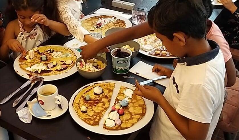 Vluchtelingkinderen versieren pannenkoeken