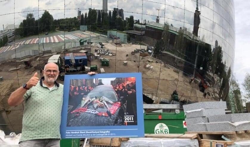 <p>Hendrik met de foto die deel uitmaakte van de tentoonstelling op de nieuwe Coolsingel.</p>