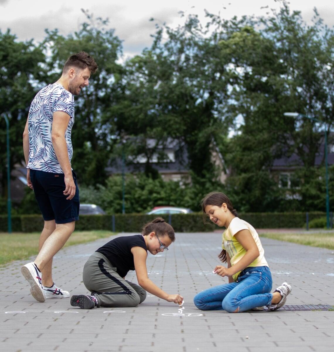 De leerlingen van Job Berkers (l) maken sommen op de stoeptegels