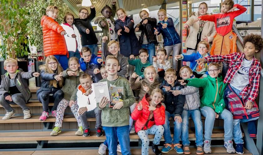 Luca met zijn boek en oorkonde. Op de achtergrond zijn klasgenootjes, die   vrijdag allemaal in de Leiderdorpse bibliotheek boeken kwamen uitzoeken.   Foto: J.P. Kranenburg