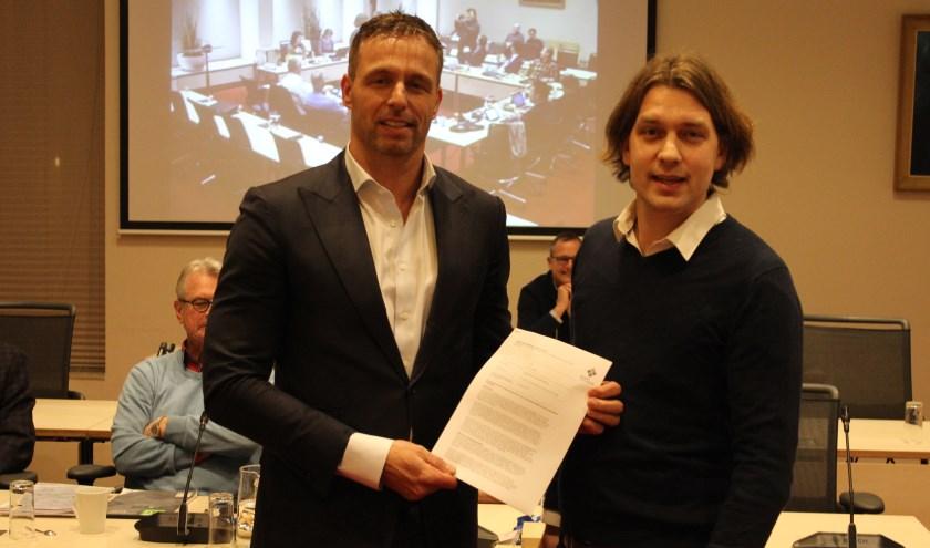 Raadslid Maarten van Welie (CDA) overhandigt het initiatiefvoorstel aan wethouder Bas Brekelmans (links). | Foto: Nico Kuyt