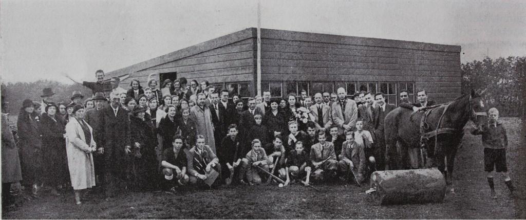 Op 18 september 1932 was de opening van de nieuwe speelvelden aan de Warmonderweg. Op de foto, vijf jaar later, zijn ze er alweer uitgegroeid. Nico Janssen spreidt zijn armen tot een welkom aan tegenstanders. Compleet met stalruimte voor het paard van de terreinknecht, dat overigens ook vaak door de heren studentenhockeyers werd gebruikt om rondjes mee over de velden te rijden. Foto: Ed Patijn © uitgeverij Verhagen