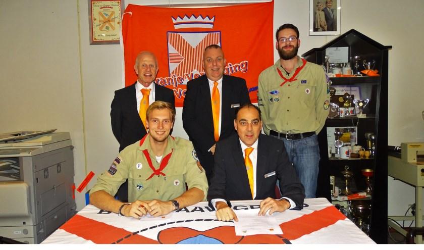 Robin Borst (Scouting Boerhaavegroep en Ton Wolvers (voorzitter Oranje Vereniging) ondertekenen de nieuwe overeenkomst.   Foto: pr.