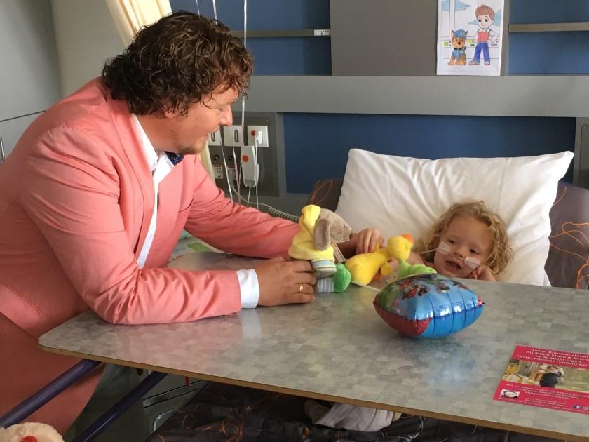 Jason Bouman geeft jonge patiënte een knuffel.