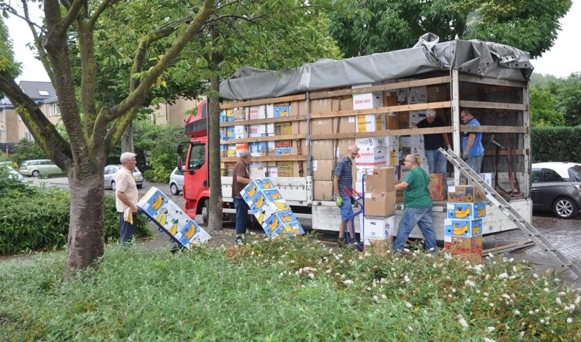 De 600 dozen met kleding, dekens en medische artikelen worden ingeladen voor transport naar zeven dorpen in Oekraine.   Foto: pr./ Henk Maat
