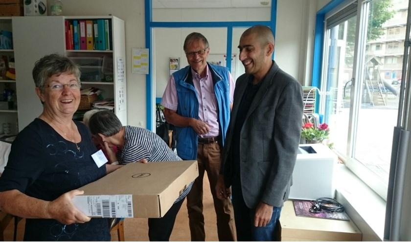 Bep Kaptijn ontvangt de nieuwe laptop uit handen van Mohammed Shaffiq.   Foto: pr.