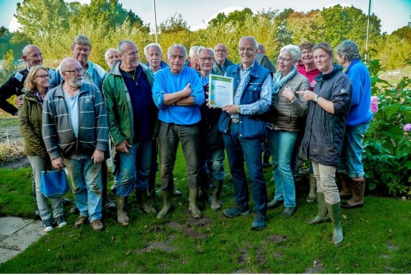 Voorzitter Joop van Huut van de schooltuinen toont de oorkonde, om hem heen staan de onmisbare vrijwilligers van schooltuinencomplex De Sterrekers.