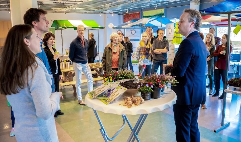 Duurzaamheidswethouder Willem Joosten opende de bewonersmarkt. Geheel links staan Marieke van Leeuwen van het MEC en Sjoerd Luiten van het IVN.