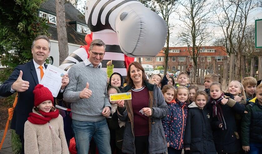 Wethouder Willem Joosten (geheel links) met locatieleider Maarten Meijers en juf Arnica Geertsema en een aantal kinderen van groep 5 bij zebra Seef, de mascotte van School op Seef.   Foto: J.P. Kranenburg